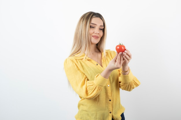 Giovane bella ragazza in camicia gialla guardando pomodoro rosso su bianco.