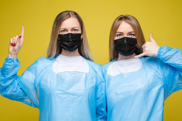 Young beautiful girls in a disposable medical gowns and with masks on their faces, portrait isolated on yellowbackground