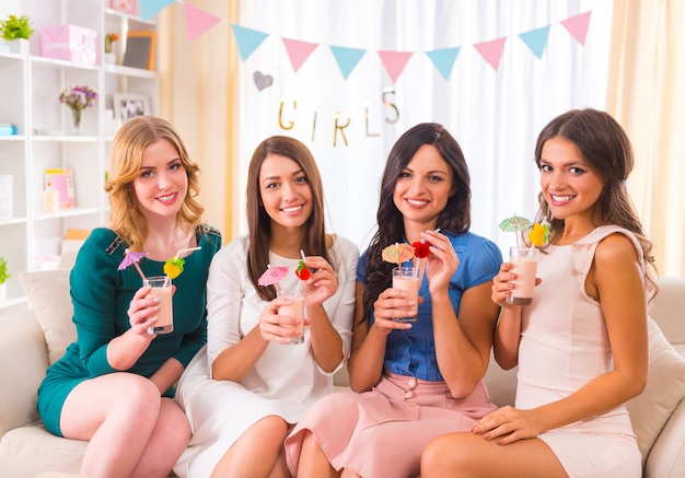Young beautiful girls drink cocktails at home party.