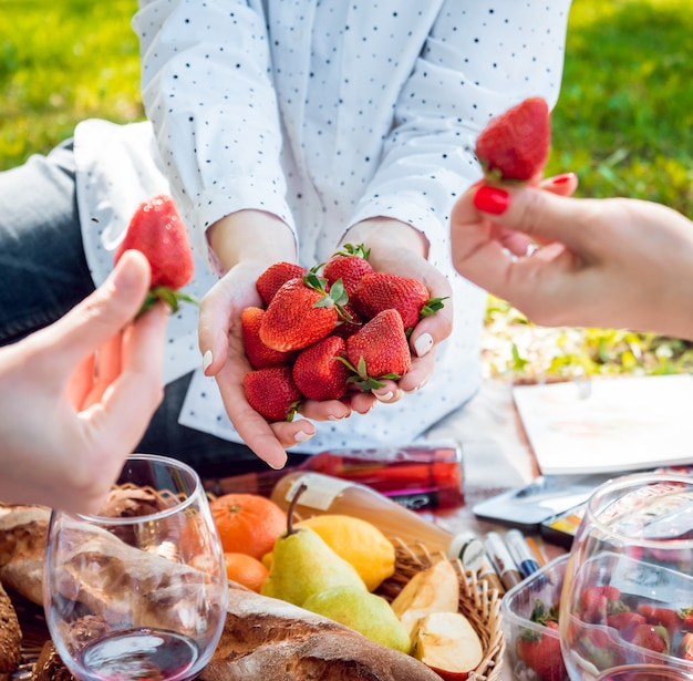 Young beautiful girls eating strawberries in the park