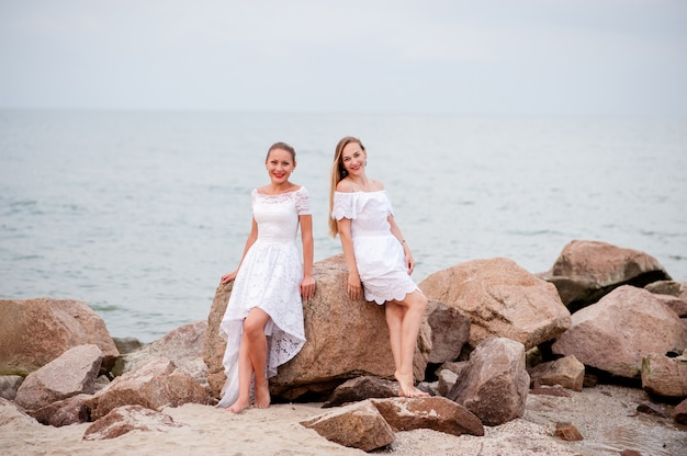 Young beautiful girls photographed on the rocks of the sea