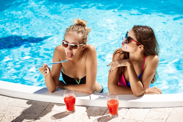 Young beautiful girls smiling, fooling, speaking, relaxing in swimming pool.