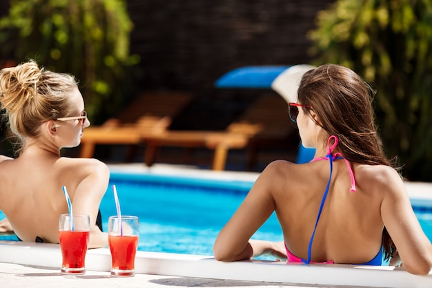 Young beautiful girls smiling, speaking, relaxing in swimming pool.