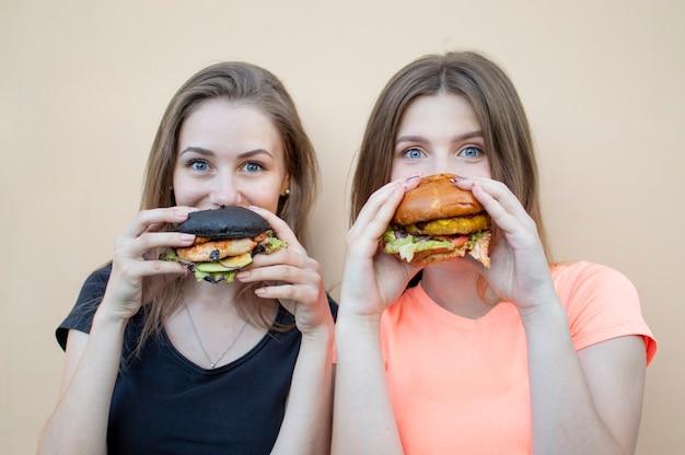 若い美しい女子学生がハンバーガーと笑顔を握る