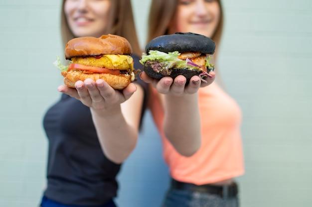 若い美しい女の子の学生は青い壁の近くに立ち、ハンバーガーを抱えて笑顔で、幸せで、チーズバーガーをカメラに映します