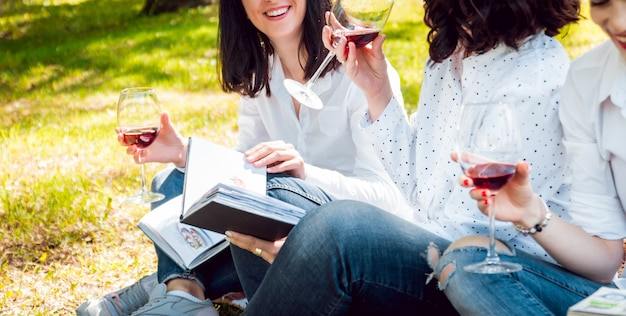 Young beautiful girls with glass of red wine and books in the park.