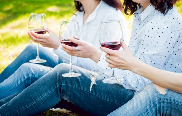 Young beautiful girls with glass of red wine in the park