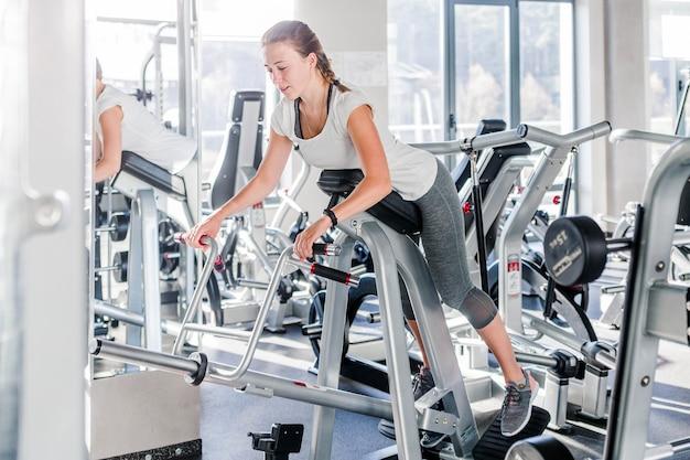 Молодая красивая хорошо подходят девушка, одетая в спортивную одежду, делает упражнения на спортивном инвентаре в современном тренажерном зале, полном солнечного света. горизонтальное фото