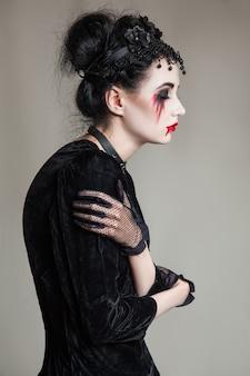 검은 칼라를 입은 피 묻은 방울과 하얀 피부와 붉은 입술을 가진 젊고 아름다운 고딕 여성