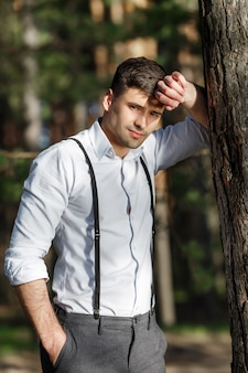 Young beautiful groom against a tree