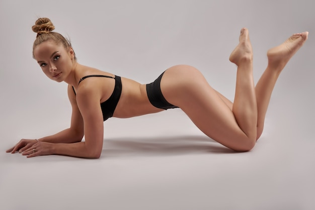 Young beautiful gymnast in sports clothes. training, gymnastics element, acrobatics on a white wall. sports motivation, stretching, banner for advertising