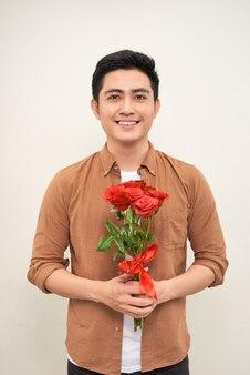 花と若い美しいハンサムな魅力的な夢中の男のカジュアルなスタイル
