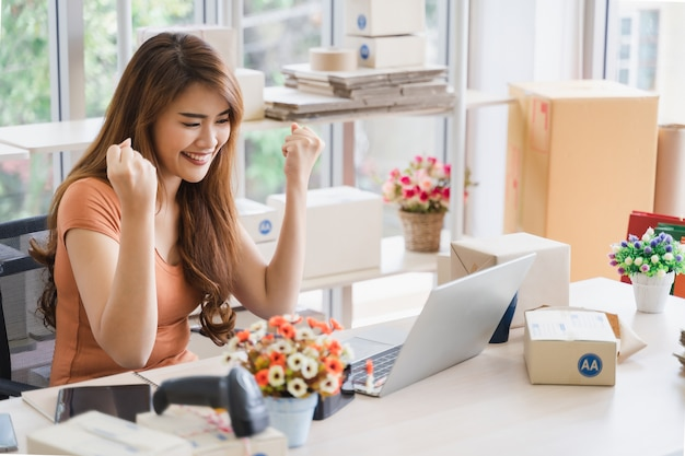 Young beautiful happy asian business woman with smiley face is using laptop with success business deals, excited by good news, woman sitting raising hand in yes gesture celebrating business success