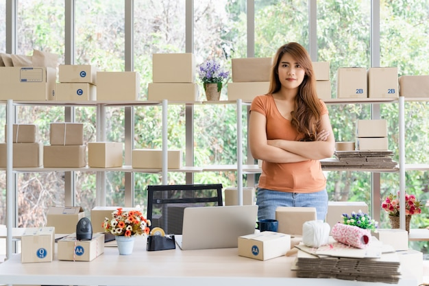Young beautiful happy asian successful business woman with smiley face is standing with arms crossed at her startup home office, woman in good feeling with business success, delivery seller concept