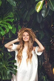 Young beautiful happy blonde girl model in hat on tropical leaves background