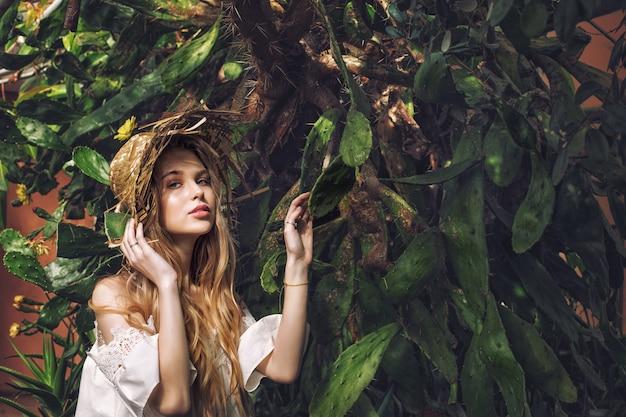 帽子の巨大なサボテンの背景に若い美しい幸せなブロンドの女の子モデル