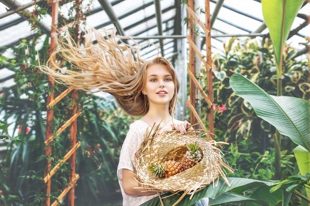 Молодая красивая счастливая блондинка модель с ананасами на фоне тропических растений в теплице