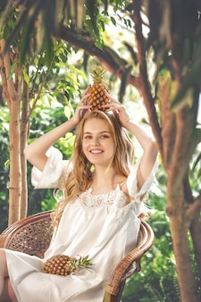 열대 식물 배경에 파인애플을 넣은 젊고 아름다운 행복한 금발 소녀 모델