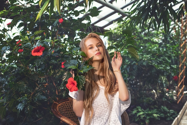 Young beautiful happy blonde girl model with red flowers on tropical plants background in greenhouse