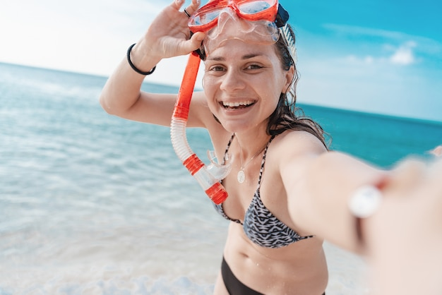 Young beautiful happy charming girl with a beautiful smile in a bikini in a mask for snorkeling takes a selfie on the seashore, outdoor activities, beach activities