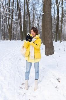 Молодая красивая счастливая жизнерадостная женщина в видео блоге зимнего леса, делает селфи-фото