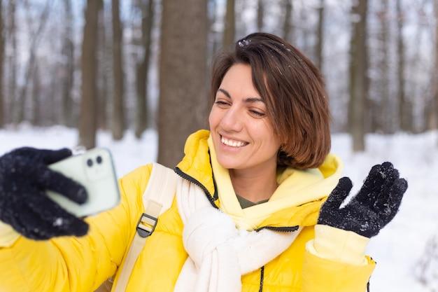 冬の森のビデオブログで若い美しい幸せな陽気な女性は、自分撮り写真を作ります