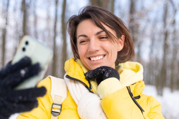 겨울 숲 비디오 블로그에서 젊은 아름 다운 행복 쾌활 한 여자는 셀카 사진을 만든다