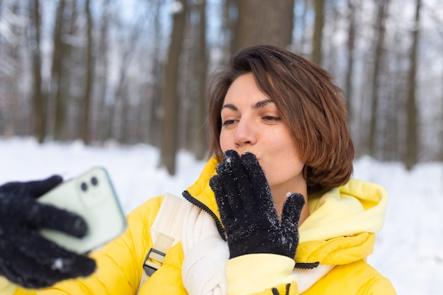 Young beautiful happy cheerful woman in the winter forest video blog, makes a selfie photo