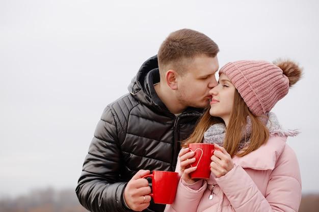 피크닉에서 젊고 아름답고 행복한 커플은 뜨거운 차를 마신다.