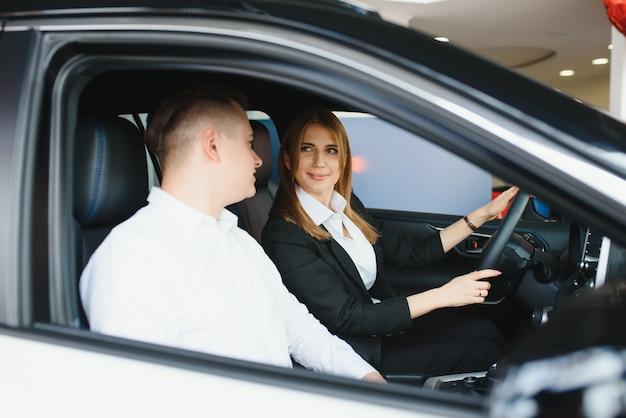 차를 사는 젊은 아름 다운 행복 한 커플. 살롱에서 아내를 위해 차를 사는 남편. 자동차 쇼핑 개념.