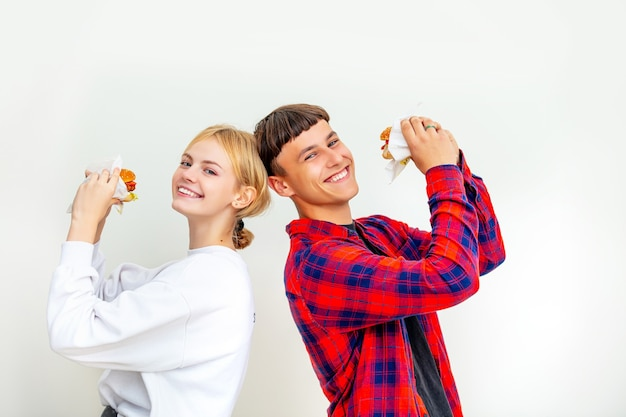 Young beautiful happy couple guy and girl eating big delicious burgers on white background