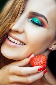 公園で夏にイチゴを保持している赤いドレスと化粧の若い美しい幸せな面白い女の子。健康的なライフスタイル、ダイエットの美しさと幸福の概念。