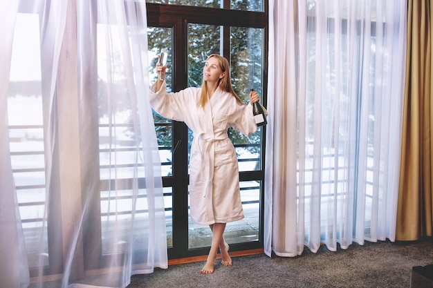 Young beautiful happy girl in a dressing gown stands at a large window with a glass