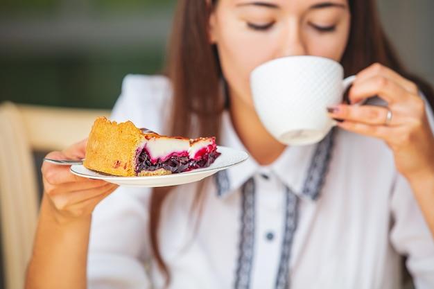 テーブルに座って朝食のコーヒーとチーズケーキを持っている若い美しい幸せな女の子