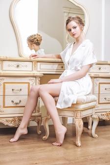 Молодая красивая счастливая девушка в белом нижнем белье и неглиже в спальне перед зеркалом