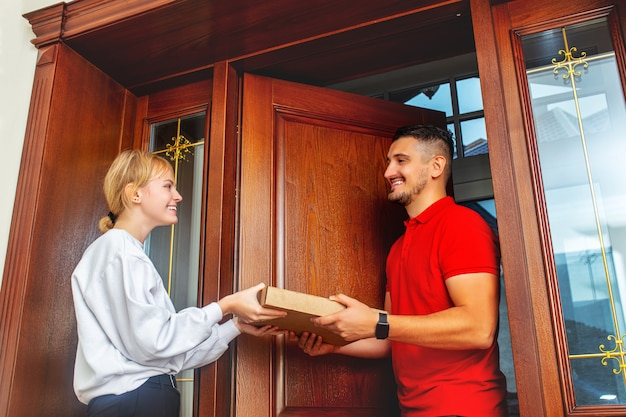 Young beautiful happy girl meets a smiling pizza delivery man at the door of the house