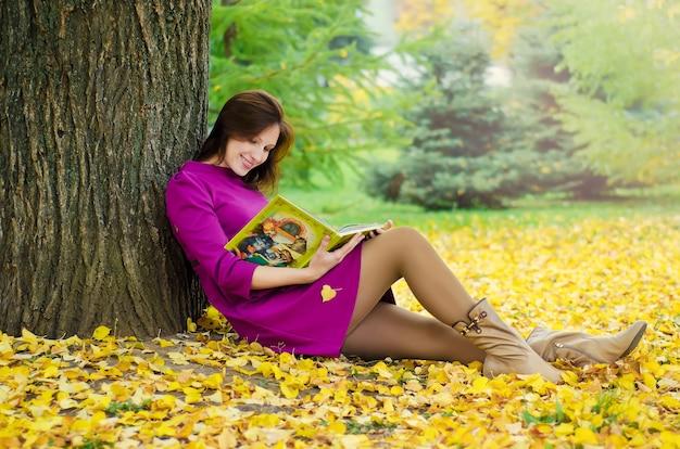 Молодая красивая счастливая девушка читает книгу под деревом осенью, сидя на желтых листьях