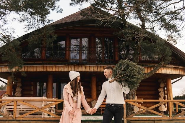 若い美しい幸せな恋人の男性と女性、木造住宅の背景に彼らの手でライブクリスマスツリーと冬のラブストーリー
