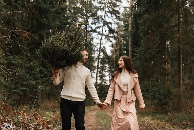 Young beautiful happy lovers man and woman, love story in winter with a live christmas tree in a pine forest in the sun