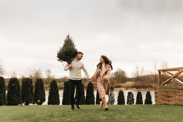 Young beautiful happy lovers man and woman, love story in winter with a live christmas tree in their hands on the background of the river bank