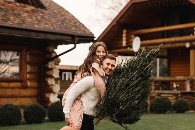 Young beautiful happy lovers man and woman, love story in winter with a live christmas tree in their hands on the background of a wooden house