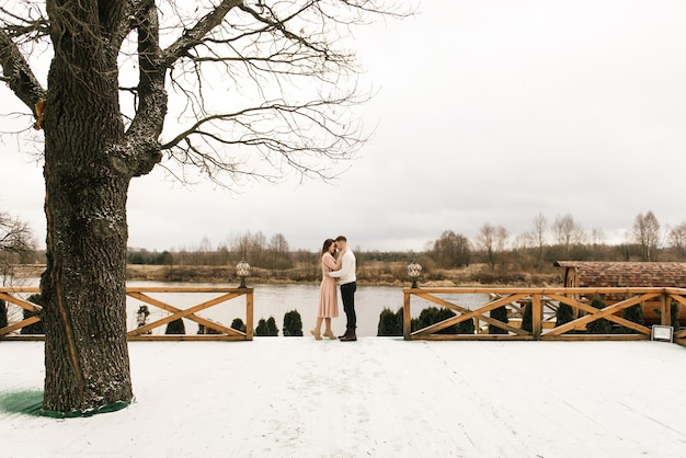 Young beautiful happy lovers man and woman, love story in winter with snow in a picturesque place