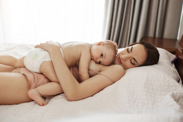 Young beautiful happy mom breastfeeding hugging her baby lying on bed at home.