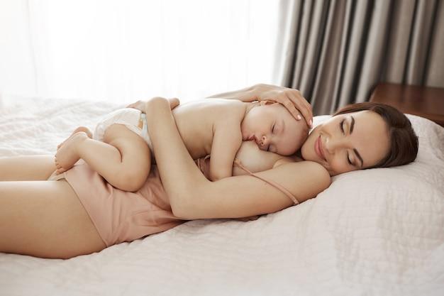 Молодая красивая счастливая мама грудью, обнимая ее ребенка, лежа на кровати у себя дома