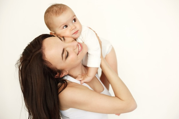 Young beautiful happy mother smiling with closed eyes holding her baby daughter over white wall.