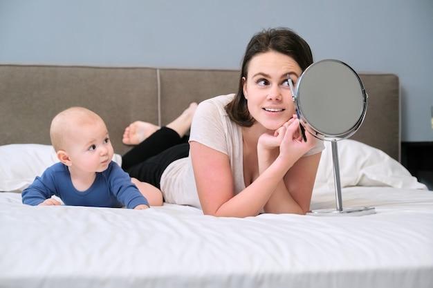 Молодая красивая счастливая мать с сыном малыша дома в постели, женщина с косметическим зеркалом делает макияж