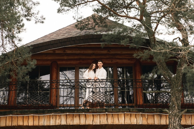 Young beautiful happy newlyweds in love a man and a woman in white bath robes on the balcony of the house smile and hug