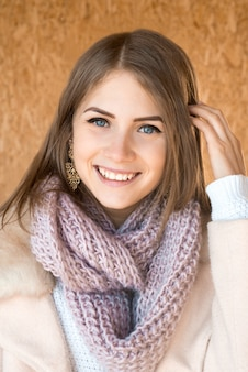 Young beautiful happy positive smiling girl with knitted scarf portrait