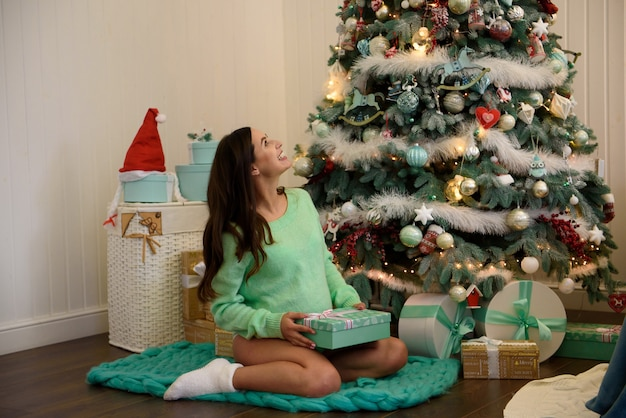 Young beautiful happy pregnant woman siting near new year tree and opening a gift