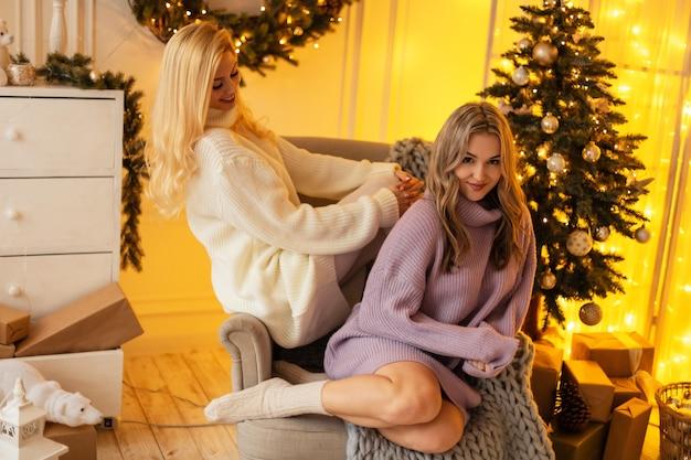 ヴィンテージのファッショナブルなセーターを着た若い美しい幸せな姉妹は、クリスマスツリー、黄色のライトと装飾の近くにニットの毛布を持ってアームチェアに座っています